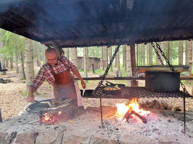 Preparing a meal over open fire.