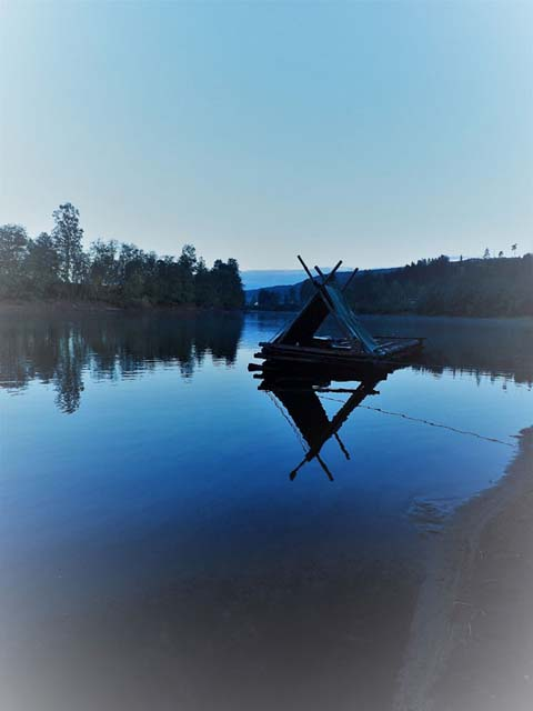 A 3m x 3m raft reflected in calm waters of the Klarälven river.